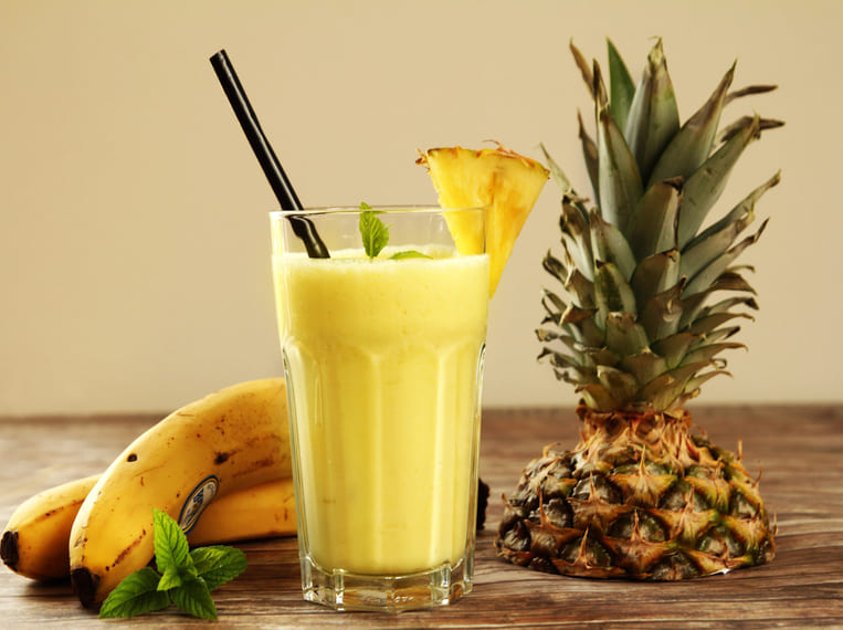 Smoothie ananas banane disposé sur une table